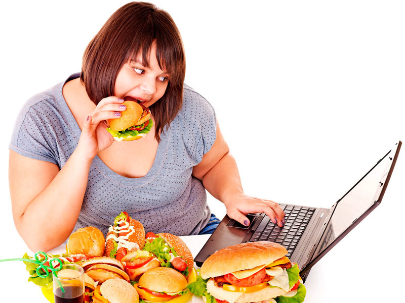 толстая девушка за ноутбуком ест фастфуд